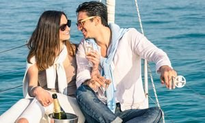 Young Couple In Love On Sail Boat With Champagne Flute Glasses –
