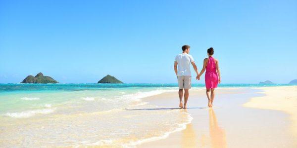Beach honeymoon couple holding hands walking on white sand beach
